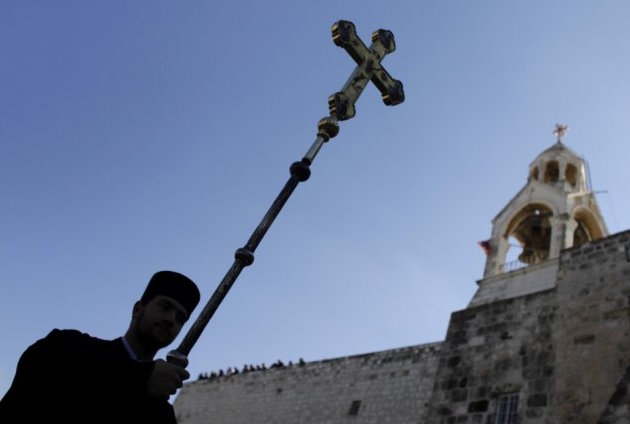 greek-orthodox-priest-carries-cross-beside-church-nativity-bethlehem-2 copy
